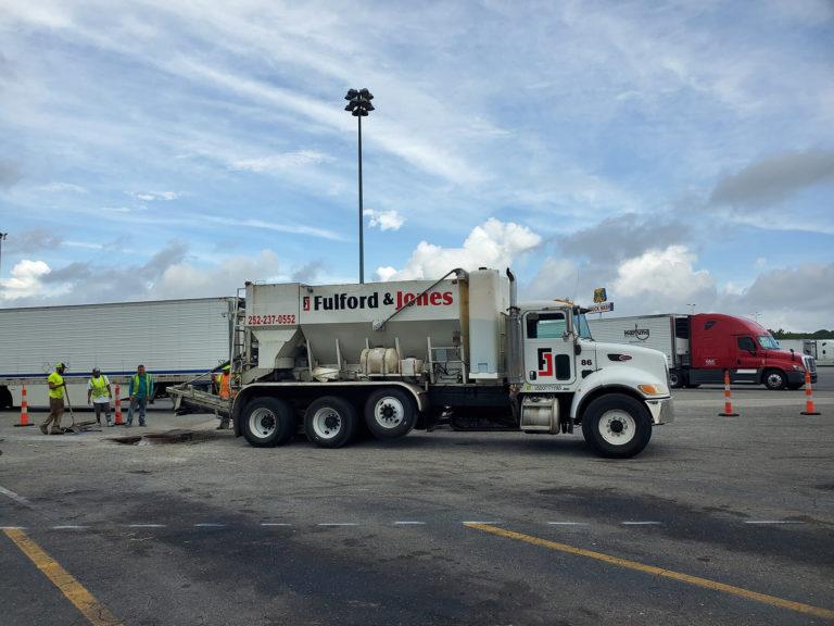 A volumetric concrete mixer pours concrete for a parking lot repair in North Carolina.