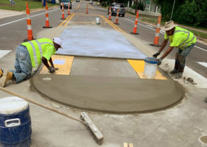 Workers finish the surface of a newly placed raised concrete median with an ADA-accessible walkway in Raleigh, NC.