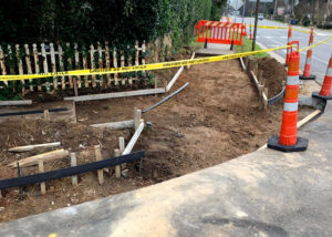 Orange pylons and yellow tape block off exposed dirt and wooden forms set up for a concrete curb and gutter replacement in Raleigh, NC.