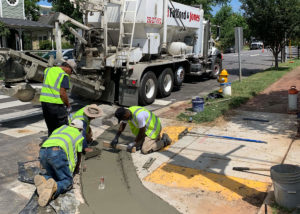 A Cemen Tech volumetric mixer sits behind workers hand screeding a newly placed ADA-accessible concrete curb in Raleigh, NC.