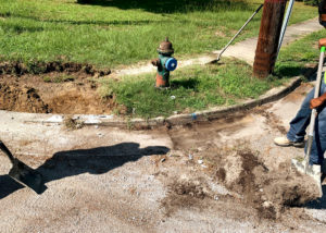 A fire hydrant is exposed on a residential street corner prior to a concrete replacement project for a curb and gutter in North Carolina.