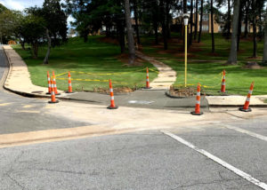 Pylons and yellow tape line off a newly placed concrete curb at a residential intersection in North Carolina.