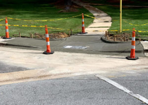 Newly placed concrete is blocked by pylons along a residential street in North Carolina.