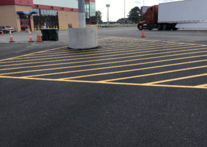 Freshly painted yellow lines show a no parking area on an asphalt parking lot in Kenly, NC.