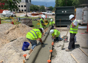 Workers use tools to form a new concrete curb and finish the surface at a Merck facility in Wilson, NC.