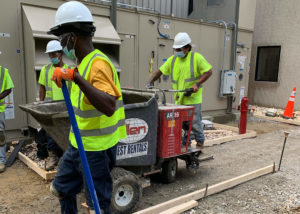A worker uses a motorized wheelbarrow to carry fresh concrete to a designated area in Wilson, NC.
