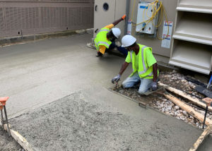 A worker trowels newly placed concrete for a walkway at a Merck facility in Wilson, NC.