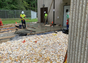 Workers look over freshly placed concrete in wooden forms at a Merck facility in Wilson, NC.