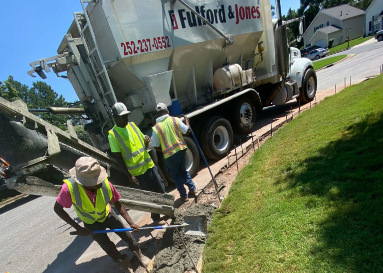 Fulford & Jones Asphalt, Inc. uses volumetric concrete mixer pours fresh concrete into a curb and gutter form in Morrisville, NC.