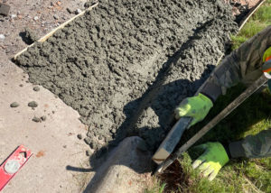 A worker uses a wood board to screed the edge of a concrete curb in Morrisville, NC.