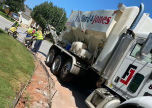 A volumetric concrete mixer pours fresh concrete into a curb and gutter form in Morrisville, NC.