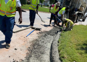 Workers use hand tools to form a newly placed concrete curb in Morrisville, NC.