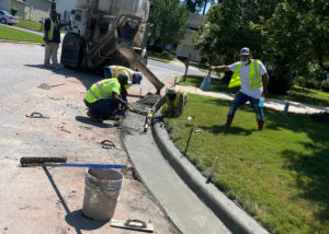 Workers screed a newly placed concrete gutter in Morrisville, NC.