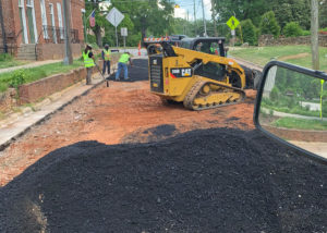 Crews spread asphalt over bare ground to replace a roadway in North Carolina.