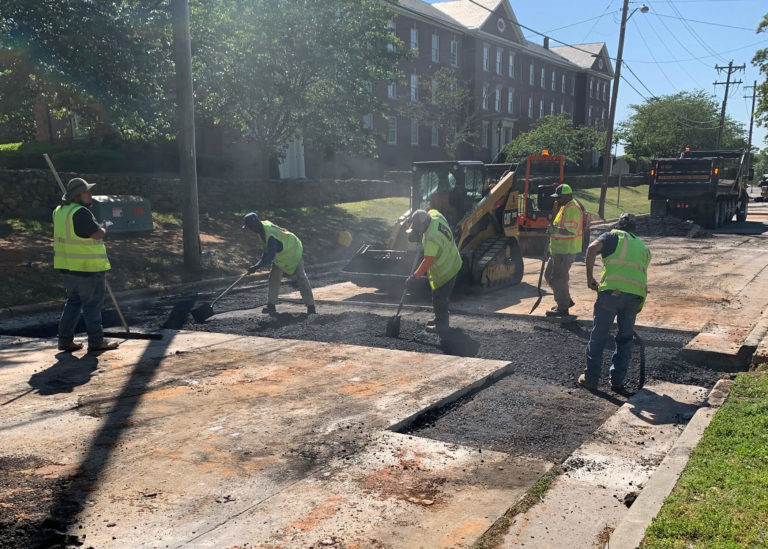 Workers use shovels to spread and place hot asphalt in a road section in North Carolina.