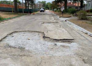 A broken asphalt paved street in North Carolina exposes rock and ground underneath.