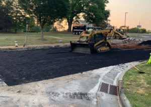 A skidloader smoothes freshly placed asphalt pavement during a street repair in eastern North Carolina.