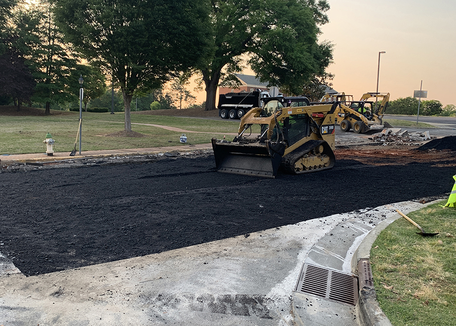 A skidsteer smooths a fresh asphalt patch during a road repair in North Carolina.
