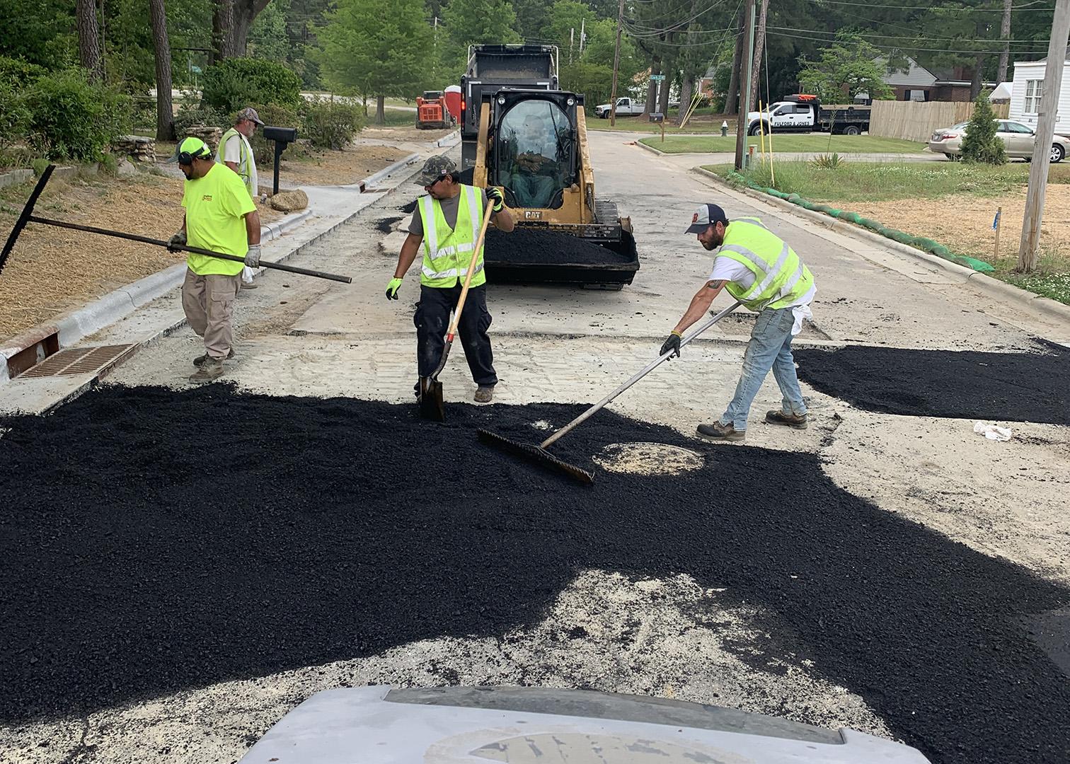 Worker spread hot asphalt during a street repair in North Carolina.