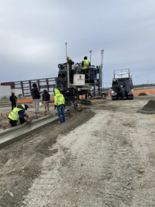 Workers in the foreground hand finish a new concrete curb while a curb machine and volumetric concrete mixer sit in the background in Kinston, NC.